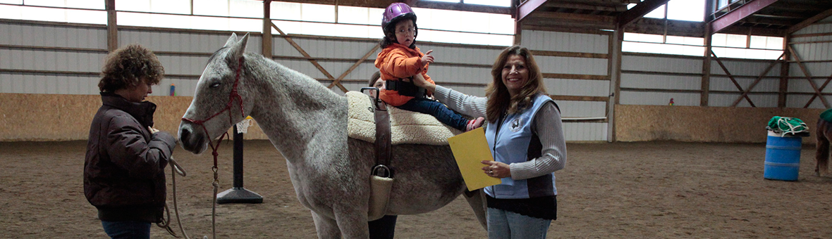 Students and volunteers participating in hippotherapy