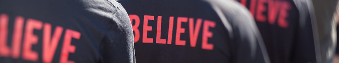 "Students walk in their ""believe"" shirts."
