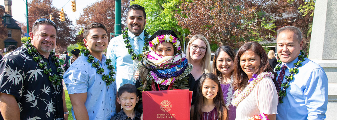 A students celebrates with her family at commencement.